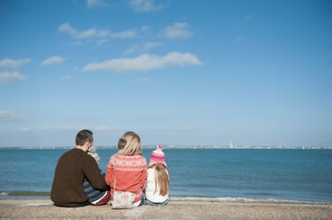 A family sits on a sea wall looking out to sea and across to Portsmouth from Ryde, Isle of Wight