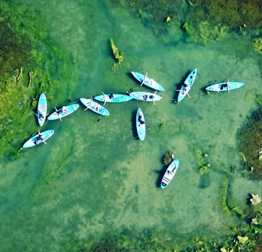 An aerial photo of people doing stand up paddleboard yoga on the River Yar on the Isle of Wight