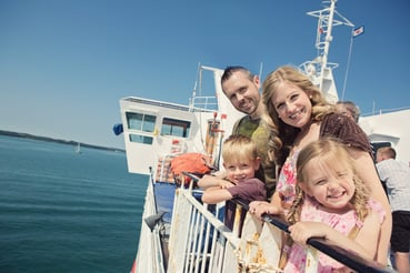Family outside on board Wightlink Ferry in summer with the sea in the background