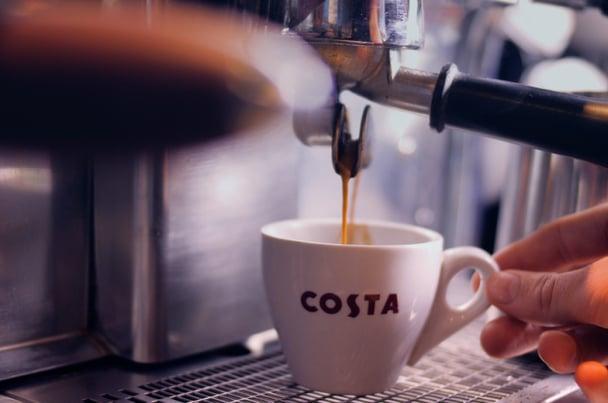 Espresso machine pouring into Costa coffee mug